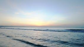 Seashore sunset horizon view. Panning right shoot. Orange Sun rising morning at ocean sunrise. Blue waves water. Luxery scene of sea with golden sunlight stock footage