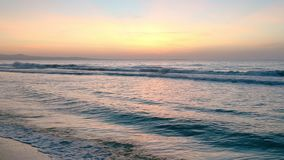 Seashore sunset side view. Golden sunset ocean horizon. Sea waves blue water and orange sunlight. Beautiful landscape calm scenery. Serene tropical panorama stock footage