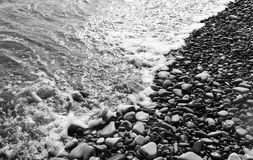 Seashore. Tide and pebbles on the beach Royalty Free Stock Photo
