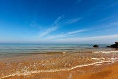 Seashore under blue sky Stock Photos