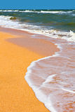 Seashore with waves and foam Stock Photos