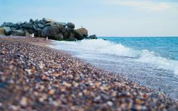 Seashore with waves and rocks at background. Defocused colorful. Seashore with waves and rocks at background. Birds at bsck. Defocused colorful sea pebbles at Stock Photo