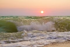 Seashore and waves on a sunset background royalty free stock image