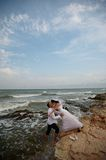 Seashore wedding (bride and groom). Beautiful newlyweds couple posing in the sea water royalty free stock photo
