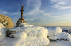 Winter sea scape with old lighthouse. Stock Photos