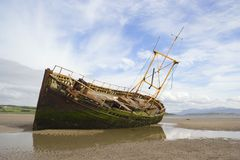 Seashore wreck. A derelict fishing boat lit by evening sunshine at Ettrick Bay, Bute stock images