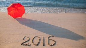Seashore z parasolem i 2015 patroszony na piasku Obrazy Royalty Free