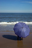 Seaside. One people hold a mbrella sit by seaside Royalty Free Stock Photography
