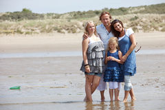 By the seaside. Beautiful young family standing on the edge of the water Royalty Free Stock Images
