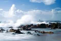 Seaside. Beautiful daylight Stormy sea with waves hitting the rocks, almost merging with the white clouds Stock Image