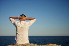 Seaside. Man sitting on rocks looking and enjoying seaside view stock image