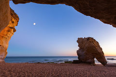 Seaside of Algarve by night. View from a cave arch by the sea at sunset Stock Photos