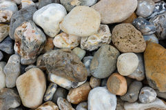 Seaside Background - Stones on a Beach. Multi-coloured stones and pebbles on a beach stock images