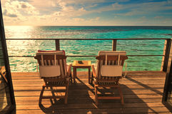 Seaside balcony with two chairs. Two deck chairs on a sea view balcony at a tropical resort in Maldives royalty free stock image