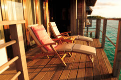 Seaside balcony with two chairs. Two deck chairs on a sea view balcony at a tropical resort in Maldives stock photography