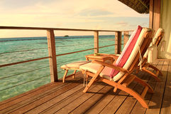 Seaside balcony with two chairs. Two deck chairs on a sea view balcony at a tropical resort in Maldives royalty free stock photos