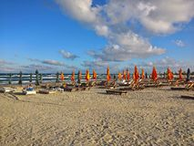 Seaside beach. Lots of beach chairs and umbrellaa on a beautiful day at seaside royalty free stock photo