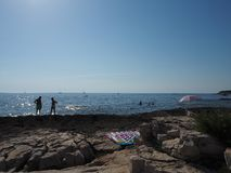 Seaside beach. Sun is shining. People on the beach. Stones Royalty Free Stock Photography