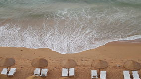 Seaside beach waves. Waves coming towards beach with chairs and umbrellas at the seaside stock footage