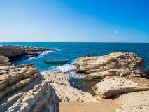 Seaside, Beirut, Lebanon. BEIRUT, LEBANON - NOVEMBER 2, 2017: Unidentified people fishing near the Pigeons` Rocks on Raouche stock photography