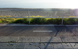Seaside bicycling route. Grass and sand along seaside bicycling concrete track with fence and sunshine along the Mediterranean on a sunny day on December 22 Stock Photography