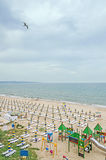The seaside, Black Sea shore with gold sands, sunbeds, blue sky, clear water, umbrellas and green vegetation. Stock Image