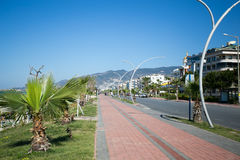 Seaside boulevar in Mediterranean town. Seaside boulevard in Mediterranean town with cobblestone payvement palms on left and automobile road and residential Stock Images