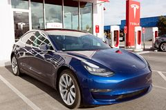 Tesla model 3 new electric car. Seaside, CA - January 6, 2018: newest navy tesla model 3 charging at supercharger station Royalty Free Stock Image