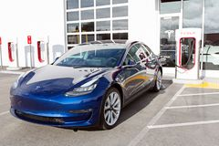 Tesla model 3 new electric car. Seaside, CA - January 6, 2018: newest navy tesla model 3 charging at supercharger station Royalty Free Stock Images