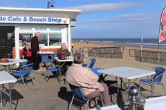 Seaside cafe and beach shop. Mablethorpe, Lincolnshire. UK. October 04, 2018. Holidaymakers relaxing in October with a sea view and drink on the promenade at stock image