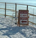 Seaside cafe sign in the snow. A seaside cafe sign in the snow with the sea beyond Royalty Free Stock Photos