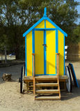 Seaside changing room bath car hut with wooden wheels in yellow and blue Stock Photo