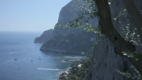 Seaside Cliffs Of Monte Castiglione Capri Italy. Medium long high angle high dynamic range shallow depth of field tracking slider shot during a sunny summer day stock footage