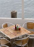 Seaside Dining For Four. A cozy corner table for four at a seaside dock cafe over looking the ocean stock photos