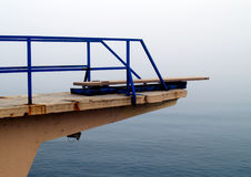 Seaside diving board in fog. A view of a high diving board over the open sea in foggy weather Royalty Free Stock Photo