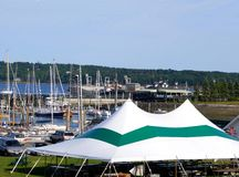Seaside events tent. With boats in the harbor background on a nice summer's day Stock Images