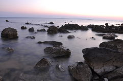 Seaside full of sharp rocks. On sunset Stock Photos