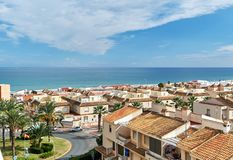 Seaside of Guardamar del Segura city. Coastal residential buildings, houses, architecture of resort town. Rooftops, urban scene. Mediterranean sea and cloudy stock photos