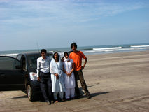 Seaside Holiday. An Indian family on their vacation on a beach with their car Stock Photography