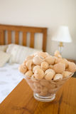 Seaside homeware. Sea shells fill a glass bowl that sits in a bedroom Stock Image