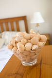Seaside homeware. Sea shells fill a glass bowl that sits in a bedroom Royalty Free Stock Photography