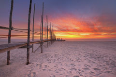 Seaside jetty at sunrise on Texel island, The Netherlands. Spectacular sunrise colours over a jetty on a beach on the island of Texel in The Netherlands Royalty Free Stock Image