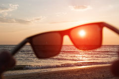 Seaside landscape with blurred sunglasses with sunset. Royalty Free Stock Photo