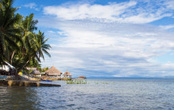 Seaside landscape with calm sea, coco palm trees lagoon and blue cloudy sky, fluffy cloud skyline. Ocean view with horizon, Philippines beach, tropic greenery Stock Image