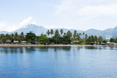 Seaside landscape with still blue water and tropical island. Sea view with distant island Royalty Free Stock Photo