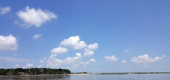 Seaside Landscape with White Clouds against Blue Sky and strip o. F Beach on the Atlantic Ocean off the coast of Savannah Georiga Royalty Free Stock Image