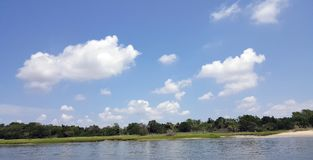 Seaside Landscape with White Clouds against Blue Sky and strip o royalty free stock photos