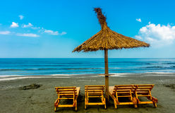 Seaside Lounge Chairs. Seaside beach with lounge chairs and straw umbrella Stock Photos