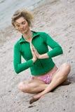 Seaside Meditation. Blond Curly Woman Meditating On Sand Near Water Stock Photos