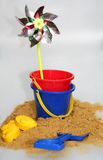 Seaside Memories. A rotating child's windmill, buckets and spades recalling seaside fun stock photo